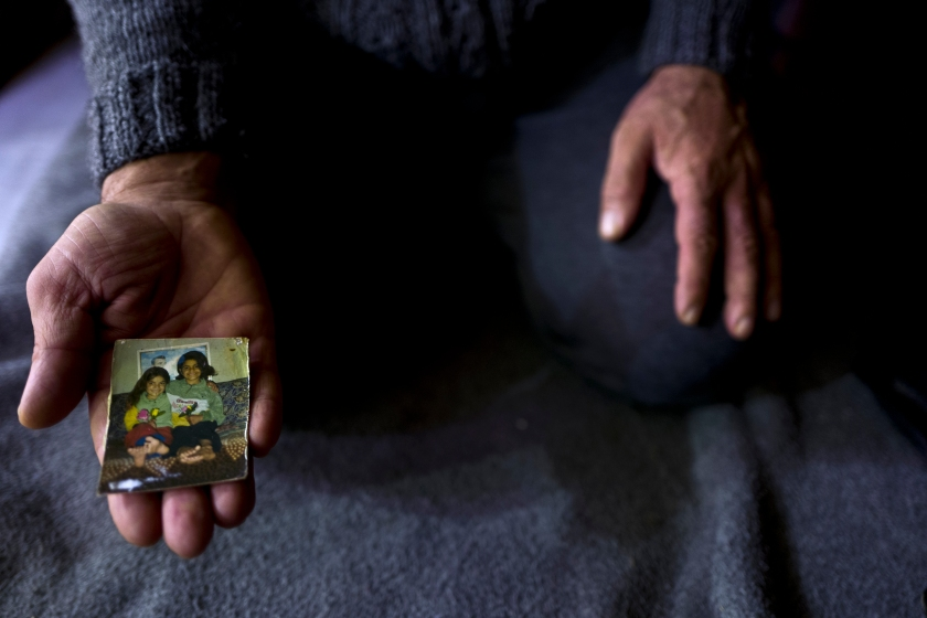 """In this Thursday, Jan. 19, 2017 photo, Ibraheem Ghareeb, 55, a Syrian refugee from al-Zohour Street in Aleppo, shows a photograph of his daughters, Mariam, when she was 7-year-old and currently 20 and lives in Germany, and his late daughter Layla, 13, who passed away in 2004 back in Syria, at his tent in Kalochori refugee camp on the outskirts of the northern Greek city of Thessaloniki. """" This is the only physical memory that I have left of my late daughter Layla and it never leave my sight."""" Ibraheem said. (AP Photo/Muhammed Muheisen)"""