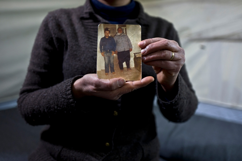 """In this Wednesday, Jan. 18, 2017 photo, Habeeba Waqas, 40, a Syrian refugee from Aleppo, holds a photograph showing her husband Mohammed and her father in law Suliman at her tent in Frakapor refugee camp on the outskirts of the northern Greek city of Thessaloniki. """"This is the only memory that I carried with me from Syria, my husband was young and handsome in this picture."""" Habeeba said. (AP Photo/Muhammed Muheisen)"""