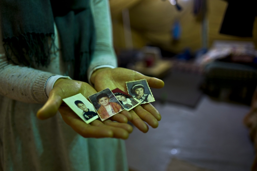 """In this Tuesday, Jan. 17, 2017 photo, Sahar Dargzini, 40, a Syrian refugee from Baghdad street in Damascus, shows photographs of her children when they were young, from right, Amal who currently is 24 and lives in Norway, Dania who currently is 26 and lives in Turkey, Mohyeddin, whose currently 15 and lives in Sweden and Salahudin whose currently 20 and lives in Sweden, at her tent in Kalochori refugee camp on the outskirts of the northern Greek city of Thessaloniki. """"I love keeping my children pictures with me all the times, they will always remain my children, I hope they will allow me to go to Norway and be with my daughter and see my granddaughter Mirna."""" Sahar said. (AP Photo/Muhammed Muheisen)"""