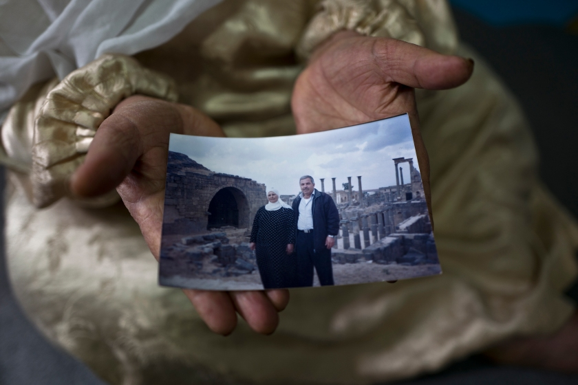 """In this Saturday, Jan. 7, 2017 photo, Amineh Hamad, 58, a Syrian refugee from Eastern Ghouta near Damascus, shows a photograph of herself and her husband Ali Abdulqader, 58, at her shelter in the Ritsona refugee camp, Greece. """"It was the last time we visited the Roman site of Busra al-Sham, a sunny Friday during the summer of 2010, we had a barbecue, walked and laughed a lot, a day from life, we miss these days, we hope one day it will come back."""" Amineh said. (AP Photo/Muhammed Muheisen)"""