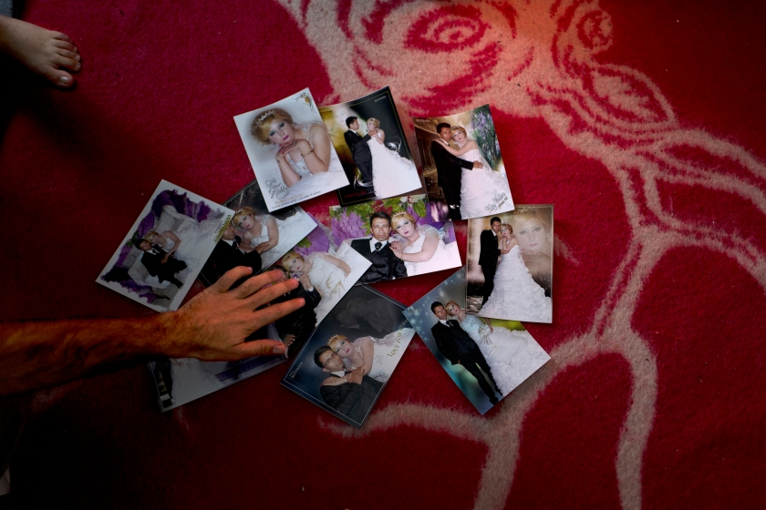 """In this Wednesday, Jan. 11, 2017 photo, Sheikhmous Hussein, 33, a Syrian refugee from the northern district of Al-Ashrafiya, Aleppo, shows photographs from his wedding day, at his shelter in the refugee camp of Ritsona, Greece. """"It was on the 8th of March 2014, these photographs were the only thing we managed to carry with us from Aleppo."""" Hussein said. (AP Photo/Muhammed Muheisen)"""