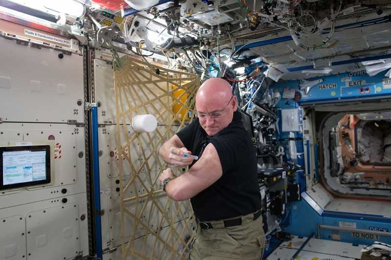 In this Sept. 24, 2015 photo made available by NASA, astronaut Scott Kelly gives himself a flu shot aboard the International Space Station for an ongoing study on the human immune system. The vaccination is part of NASA's Twins Study, a compilation of multiple investigations that take advantage of a unique opportunity to study identical twin astronauts Scott and Mark Kelly, while Scott spends a year aboard the station and Mark remains on Earth. (NASA via AP)