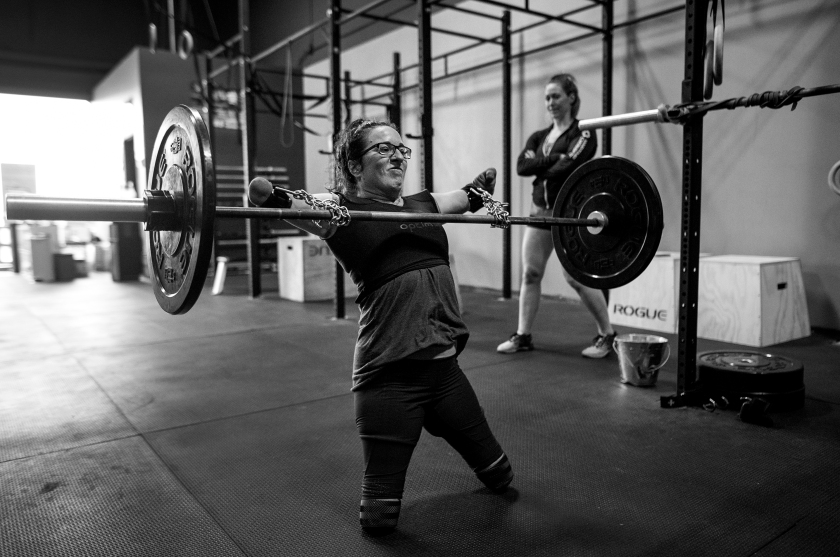 """Sports - Third Prize, Stories: With the aid of chains purchased at the hardware store and deadlift straps, Lindsay performs snatches under the watchful eye of coach and co-owner of CrossFit OnSide Jenny Jeffries in Halifax, Nova Scotia, Canada on July 8, 2016. """"It's been an important relationship for me"""", says Jeffries, who was admittedly affected by her mother's disabilities following a car accident. """"How could it not - seeing Lindsay doing what she's been doing her whole life."""" (Darren Calabrese for ESPN)"""