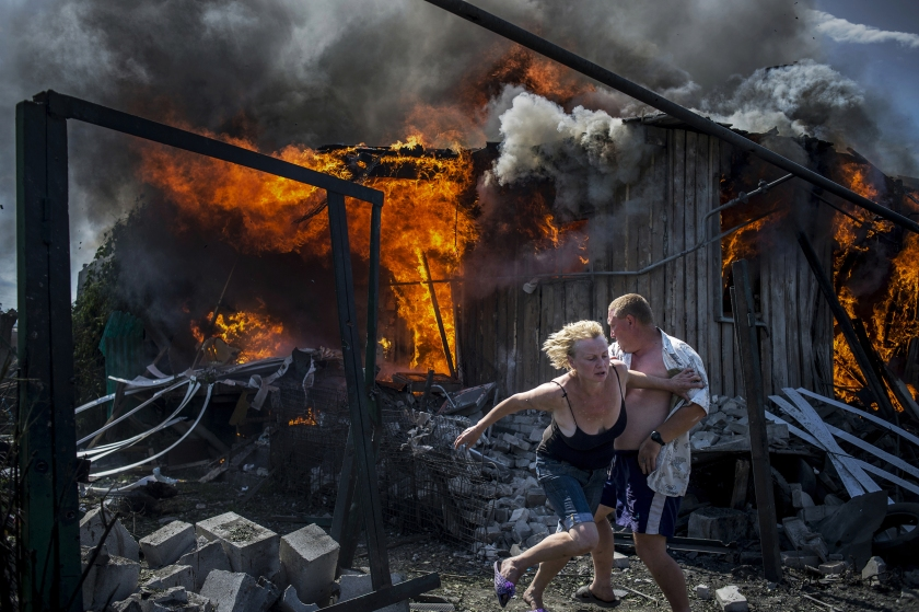 Long-Term Projects - First Prize: Civilians escape from a fire at a house destroyed by the air attack in the Luhanskaya village. (Valery Melnikov for Rossiya Segodnya)