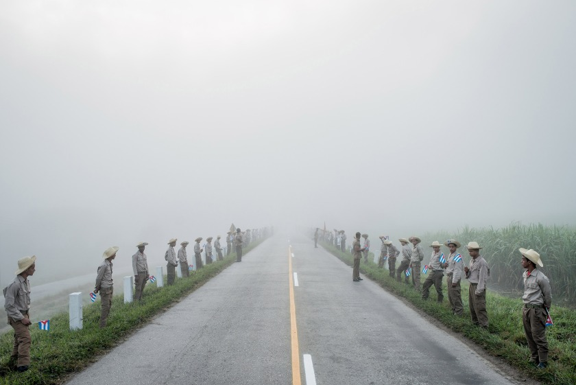 Daily Life - First Prize, Stories: Members of the Ejercito Juvenil del Trabajo waited along the road to Santiago de Cuba at dawn for Fidel Castro's caravan on December 3, 2016. Cuba declared nine days of mourning after Fidel Castro's death, a period that culminated with his funeral. In December, days after Fidel Castro's death, his ashes were taken into the countryside, on a route that retraced, in reverse, the steps of the revolution he led in 1959. Towns and villages along the route were emptied of residents as thousands tried to catch a glimpse of Castro's remains. For many, the death of Fidel Castro felt like that of a father. In death, as in life, Fidel Castro demanded reverence. Cuba brims with life, a contrast drawn sharper amid its faded grandeur. From one end of the country to the other, thousands of Cubans waited to bid farewell to Fidel. (Tomas Munita for The New York Times)