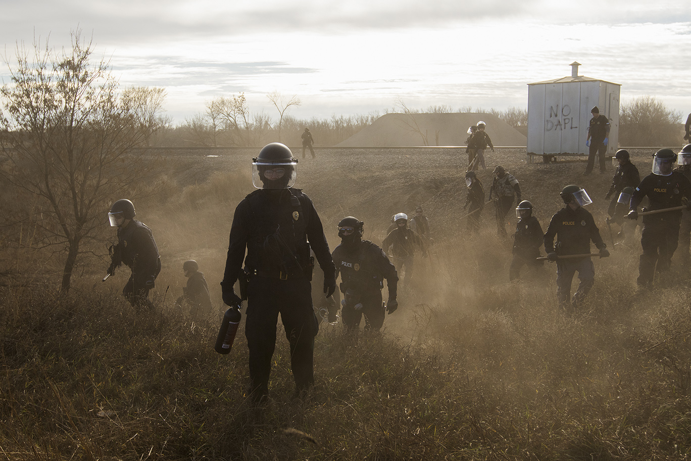 Contemporary Issues - First Prize, Stories: Riot police clear marchers from a secondary road outside a Dakota Access Pipeline (DAPL) worker camp using rubber bullets, pepper spray, tasers and arrests. In other incidents they've employed militarized vehicles, water canons, tear gas and have been accused of using percussion grenades. For nearly 10 months, members of the Standing Rock Sioux tribe and their allies camped out in opposition to the Dakota Access Pipeline crossing their territory and threatening their water supply. The estimated $3.78 billion project, backed by Energy Transfer Partners, is nearly complete, covering almost 1,172 miles. In military vehicles and body armor, police used tear gas, pepper spray, rubber bullets, and water cannons against the protesters, and have been accused of inhumane treatment of arrestees. (Amber Bracken)