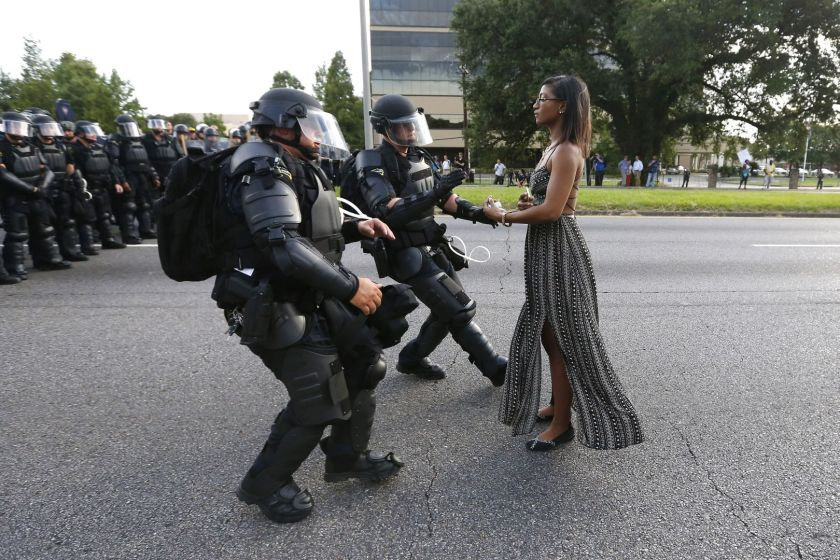 Contemporary Issues - First Prize, Singles: Lone activist Ieshia Evans stands her ground while offering her hands for arrest as she is charged by riot police during a protest against police brutality outside the Baton Rouge Police Department in Louisiana, USA, on 9 July 2016. Evans, a 28-year-old Pennsylvania nurse and mother of one, traveled to Baton Rouge to protest against the shooting of Alton Sterling. Sterling was a 37-year-old black man and father of five, who was shot at close range by two white police officers. The shooting, captured on a multitude of cell phone videos, aggravated the unrest coursing through the United States in previous years over the use of excessive force by police, particularly against black men. (Jonathan Bachman/Thomson Reuters)