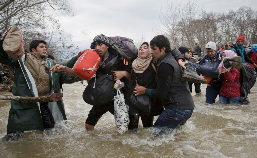 Contemporary Issues - Second Prize, Singles: A woman is supported by two men while crossing a river, as refugees attempt to reach Macedonia on a route that would bypass the border fence, on 14 March 2016. Hundreds of refugees walked out of an overcrowded camp on the Greek-Macedonian border on this day, shortly after the closure of Macedonia's borders, determined to head north despite the dangers of the crossing. (Vadim Ghirda/The Associated Press)