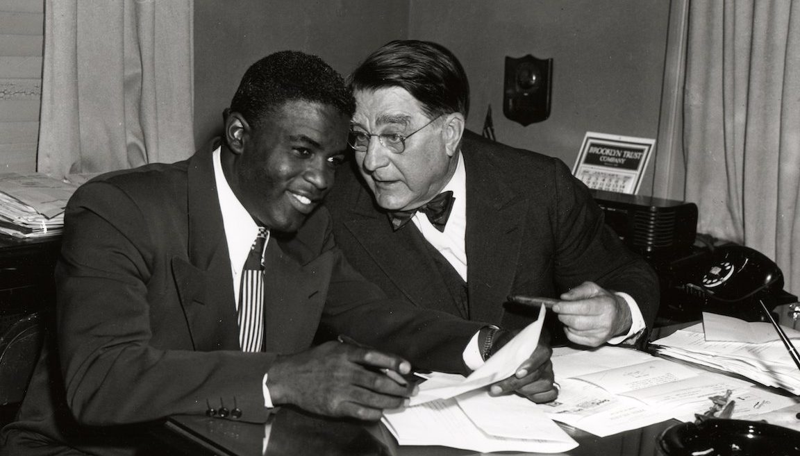 BROOKLYN - 1949.  Jackie Robinson, left, and Branch Rickey share a joke during a contract signing session in the front offices of the Brooklyn Dodgers at Ebbets Field in Brooklyn in 1949.   (Photo by Mark Rucker/Transcendental Graphics, Getty Images)
