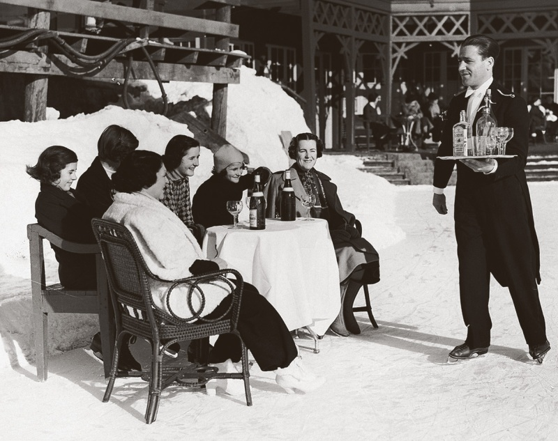 An ice-skating waiter in St. Moritz, Switzerland, delivers gin and soda to British ladies, 1920s (Hulton-Deutsch Collection/CORBIS/Corbis via Getty Images)