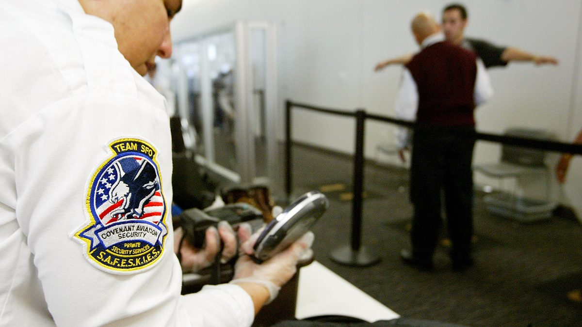 A Transportation Security Administration baggage screener inspects an electronics device as a man is screened in the background at the international terminal of San Francisco International Airport August 5, 2003 in San Francisco, California. The TSA told screeners today to pay close attention to cameras, laptop computers and cell phones, addressing a concern that terrorists could attempt to hide explosives in electronic devices.  (Justin Sullivan/Getty Images)