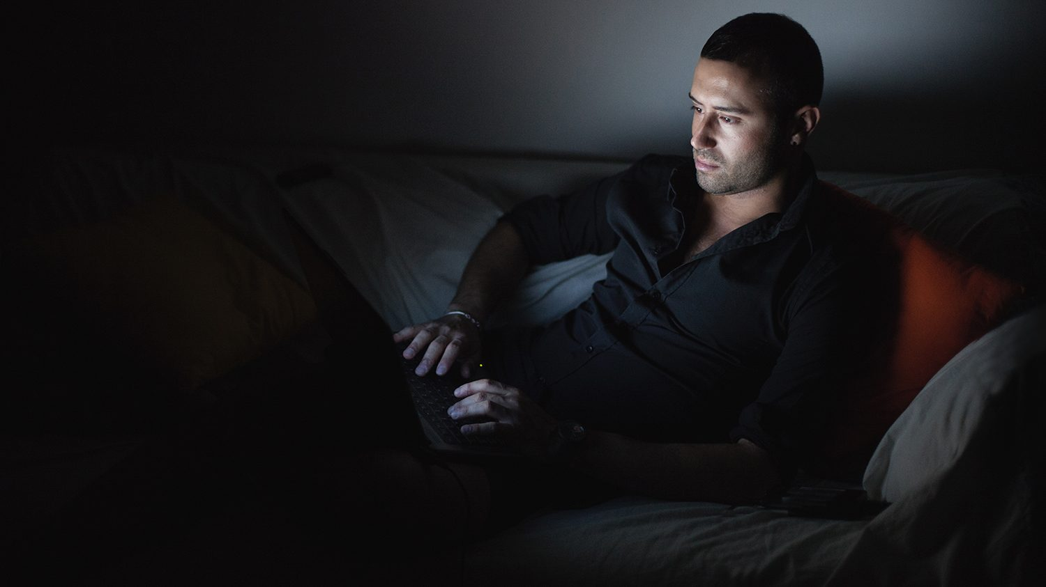 Man lying on sofa and working on his laptop at night.
