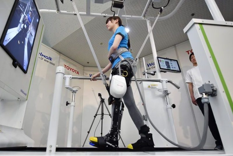 A model demonstrates how the rehabilitation-assist robot Welwalk WW-1000, developed by Japan's Toyota Motor Corporation, helps to assist in flexing and extending the knee while walking on a treadmill during a press preview in Tokyo on April 12, 2017. (Kazuhiro Nogi/AFP/Getty Images)