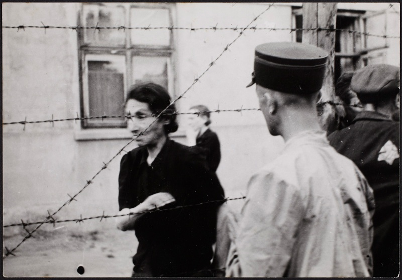 Lodz ghetto: Ghetto police with woman behind barbed wire (Henryk Ross/Art Gallery of Ontario)