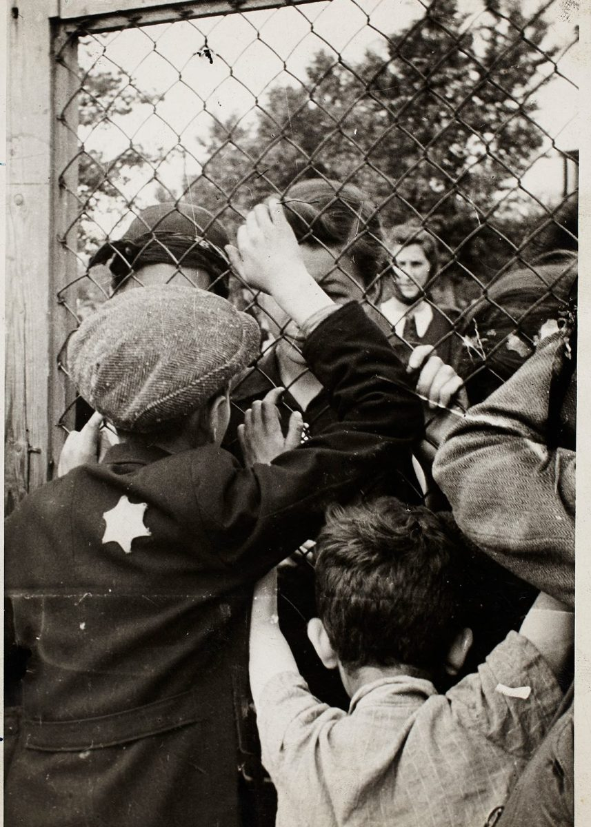 Lodz ghetto: Children talking through fence of central prison on Czarnecki Street prior to deportation (Henryk Ross/Art Gallery of Ontario)