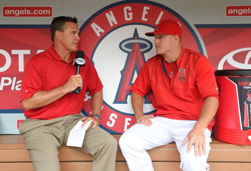 ANAHEIM, CA - JUNE 28: Former Los Angeles Angels of Anaheim player Tim Salmon interviews Mike Trout #27 of the Los Angeles Angels of Anaheim in the dugout before the game against the Seattle Mariners at Angel Stadium of Anaheim on June 28, 2015 in Anaheim, California. (Photo by Matt Brown/Angels Baseball LP/Getty Images)