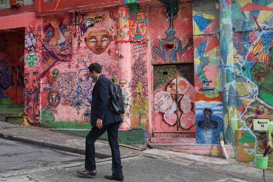 A pedestrian passes in front of walls displaying graffiti and pichacao in Sao Paulo, Brazil (Patricia Monteiro/Bloomberg)