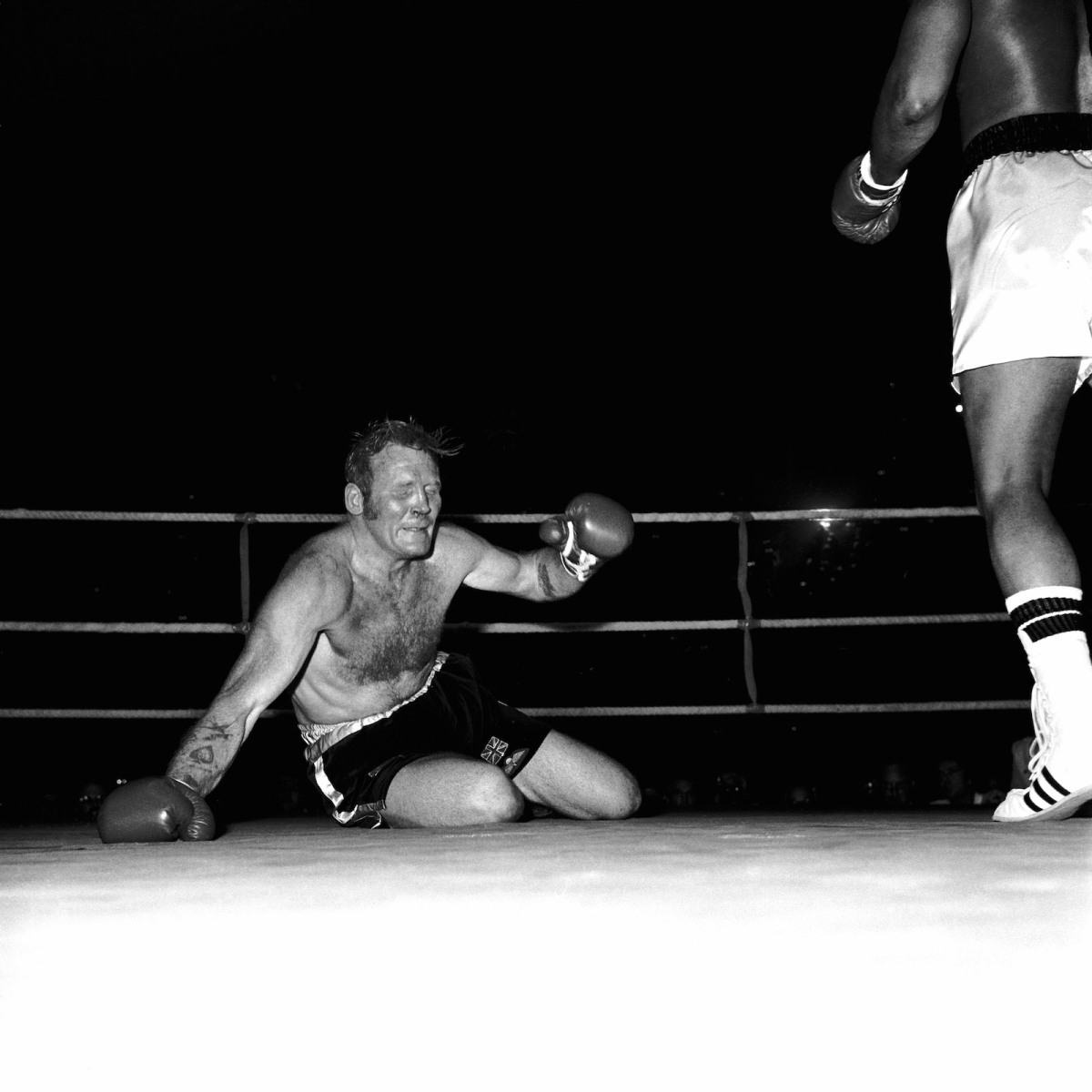 Richard Dunn grimaces as he hits the canvas again, one of five knockdowns he suffered during his 1976 fight against Muhammad Ali, one of boxing's great mismatches.  (PA Images via Getty Images)