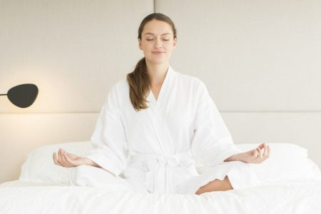 Serene woman in bathrobe meditating in lotus position on bed.