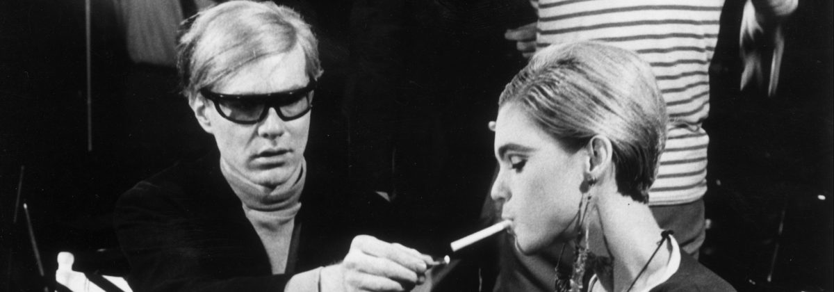 American Pop artist Andy Warhol (1928 - 1987) sits next to actor Edie Sedgwick (1943 - 1971) and lights her cigarette, on the set of one of his films.  (Walter Daran/Hulton Archive/Getty Images)