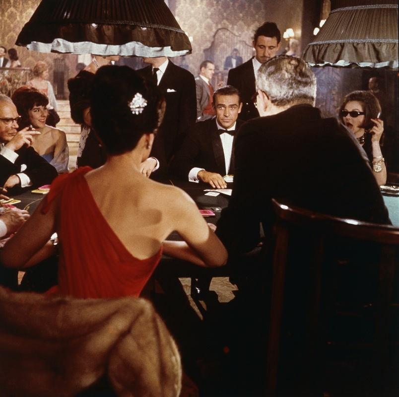 Scottish actor Sean Connery (center) as fictional secret agent James Bond sits at a casino card table in a scene from the film 'Dr. No,' directed by Terence Young, 1962. British actress Eunice Gayson sits with her back to the camera in a red, off the shoulder dress. (MGM Studios/Courtesy of Getty Images)