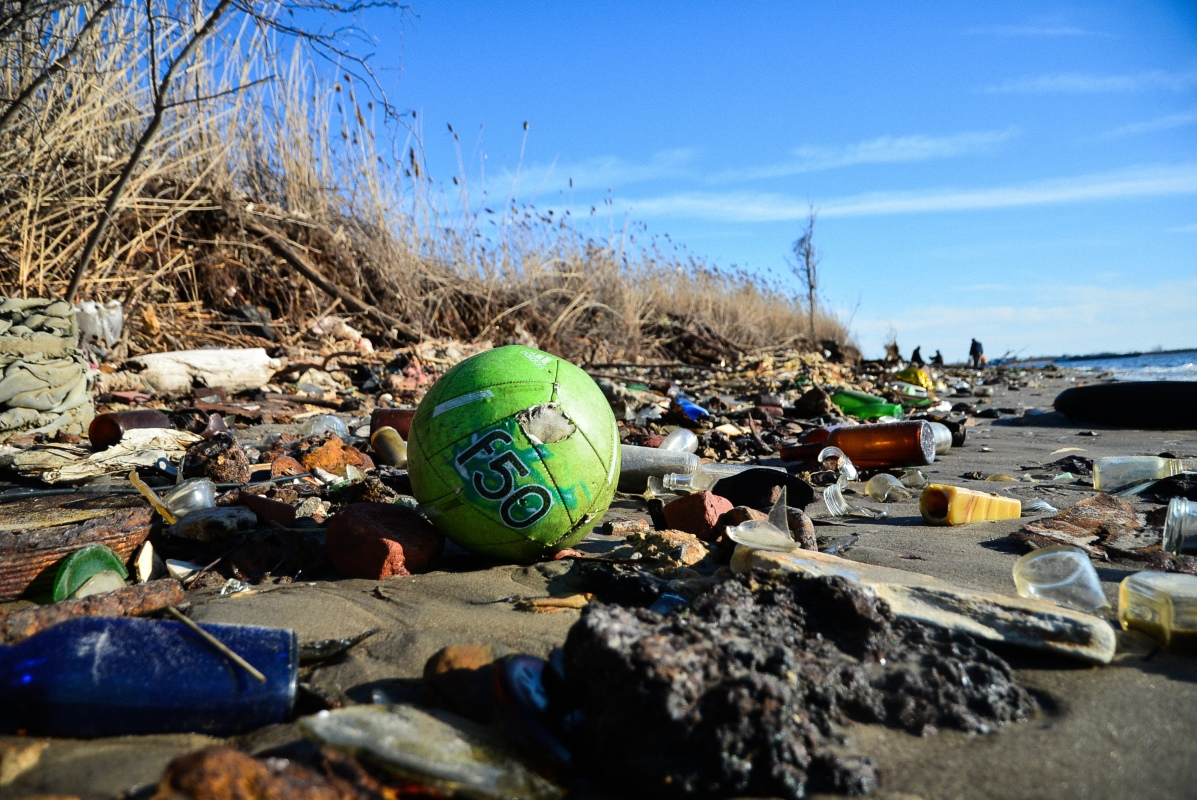 A soccer ball, broken bottles and other trash wash ashore at Dead Horse Bay. March 11, 2018. (Diana Crandall)