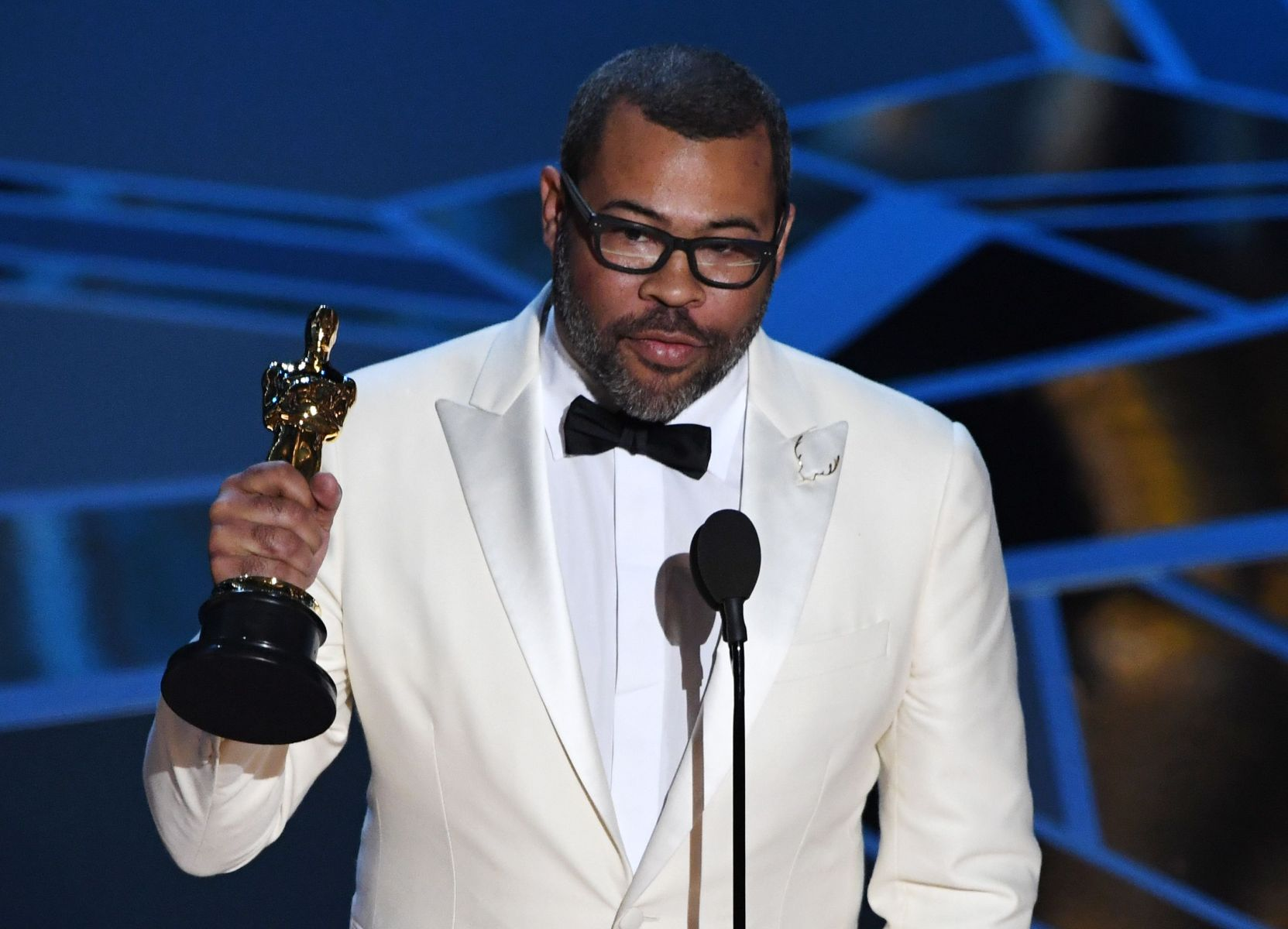 "TOPSHOT - Director Jordan Peele delivers a speech after he won the Oscar for Best Original Screenplay for ""Get Out"" during the 90th Annual Academy Awards show on March 4, 2018 in Hollywood, California. / AFP PHOTO / Mark Ralston        (Photo credit should read MARK RALSTON/AFP/Getty Images)"
