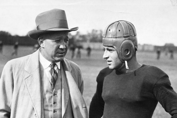 Notre Dame football coach Knute Rockne talks with a player. (George Rinhart/Corbis via Getty Images)