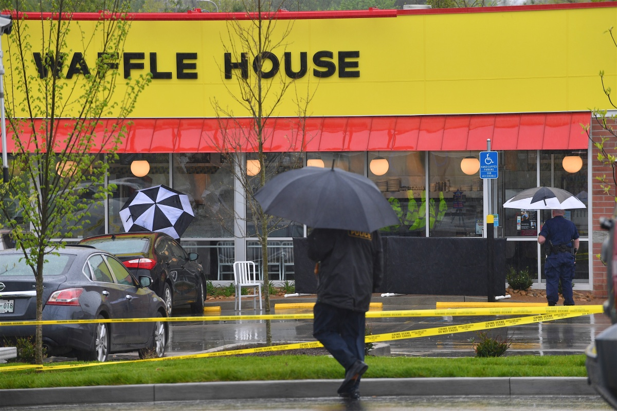 Law enforcement stand outside a Waffle House where four people were killed and two were wounded after a gunman opened fire with an assault weapon on April 22, 2018 in Nashville, Tennessee. Travis Reinking, 29, of Morton, IL, is person of interest in the shooting and is suspected to have left the scene naked. (Photo by Jason Davis/Getty Images)