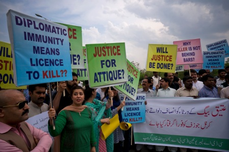 """Pakistani protesters stage a rally demanding a trial for American diplomat involved in a vehicle crash that killed a person, in Islamabad, Pakistan, Tuesday, April 10, 2018. Police have requested the government impose a travel ban on an American diplomat involved in a vehicle crash over the weekend that killed one Pakistani man and injured another in the capital Islamabad. Banner reads """"give justice to the family of Ateeq Baig, arrest Col. Joseph."""" (AP Photo/B.K. Bangash)"""