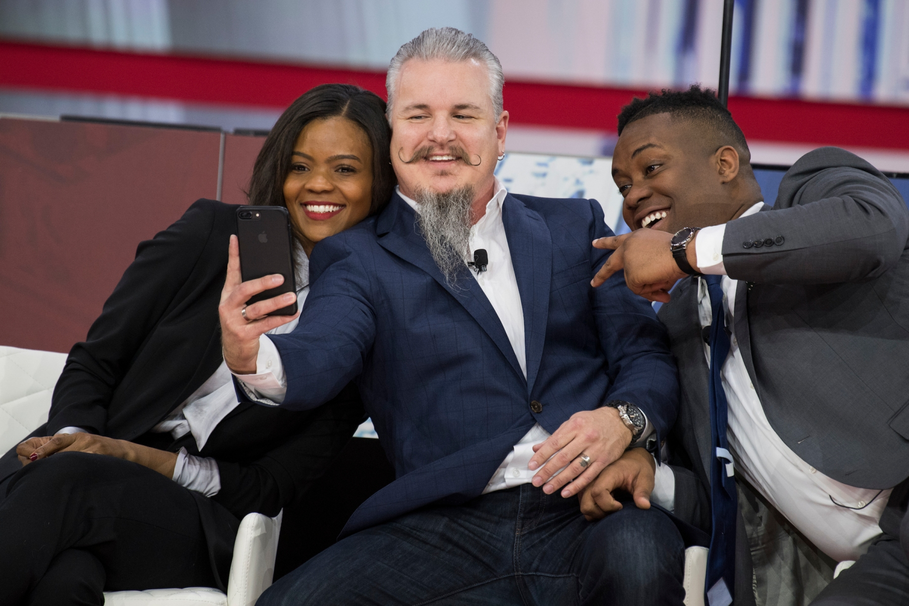 From left, Candace Owens, Chris Loesch, and Lawrence Jones III, take a selfie on stage at the Conservative Political Action Conference at the Gaylord National Resort in Oxon Hill, Md., on February 22, 2018. (Photo By Tom Williams/CQ Roll Call)