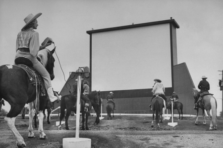 Horseback riders in cowboy garb, taking positions at speaker posts while settling in to watch the evening's feature at a Drive-In movie theater.  (Photo by Carl Iwasaki/The LIFE Images Collection/Getty Images)