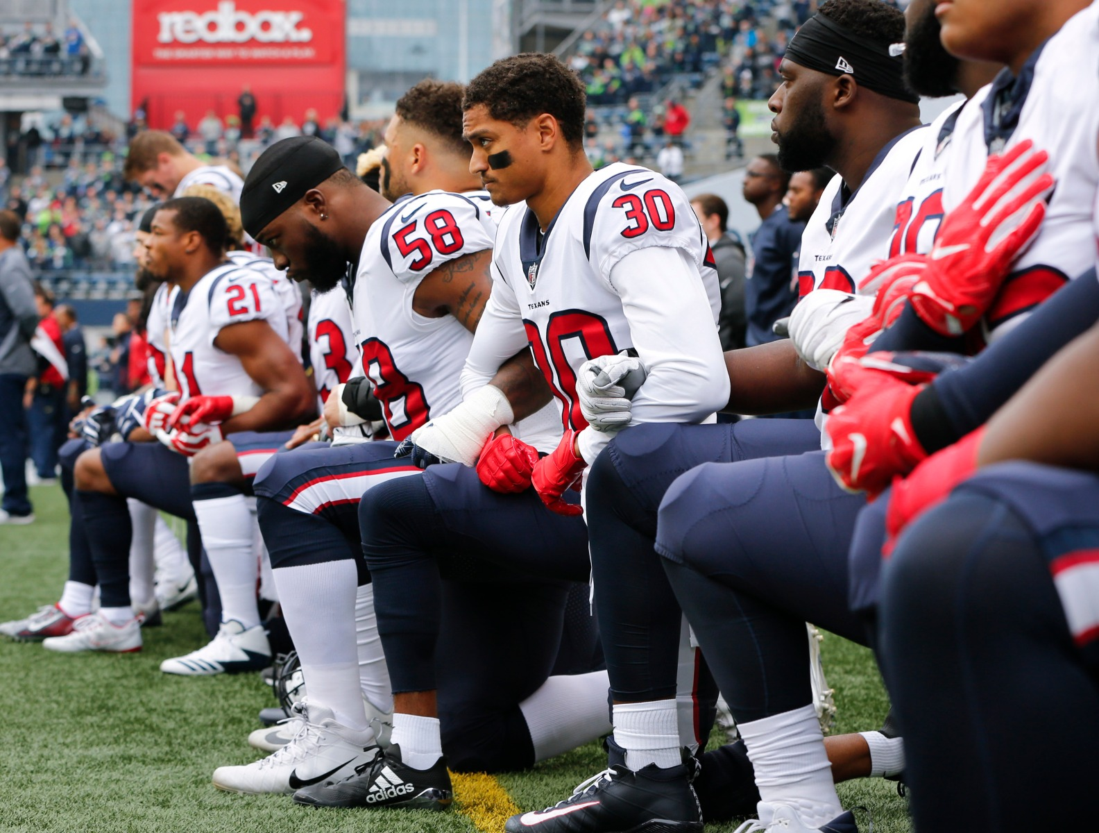 Members of the Houston Texans, including Kevin Johnson #30 and Lamarr Houston #58, kneel during the national anthem before the game at CenturyLink Field on October 29, 2017 in Seattle, Washington.  (Jonathan Ferrey/Getty Images)