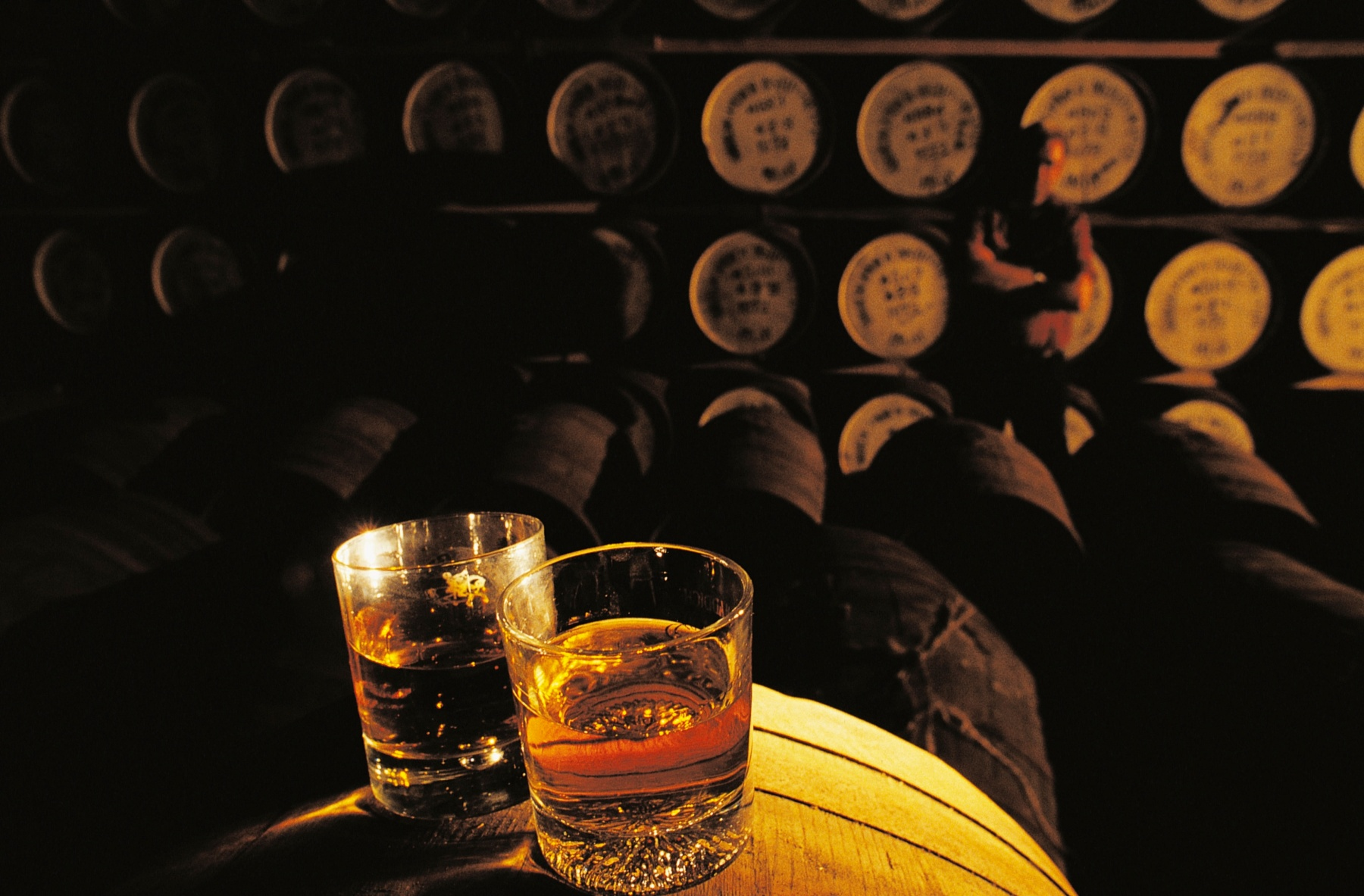 Whiskey glasses on a barrel in a whiskey distillery, Hebrides, United Kingdom.