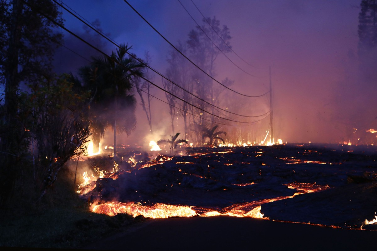 Lava from a Kilauea volcano fissure advances up a residential street in Leilani Estates, on Hawaii's Big Island, on May 27, 2018 in Pahoa, Hawaii. Lava also flowed to a geothermal power plant today raising fears that toxic gas could be released if wells are breached by lava. The Big Island, one of eight main islands that make up Hawaii state, is struggling with tourist bookings following the Kilauea volcano eruptions, with summer bookings at the island down 50 percent. Officials stress that the eruptions have thus far only affected a small portion of the island.  (Photo by Mario Tama/Getty Images)