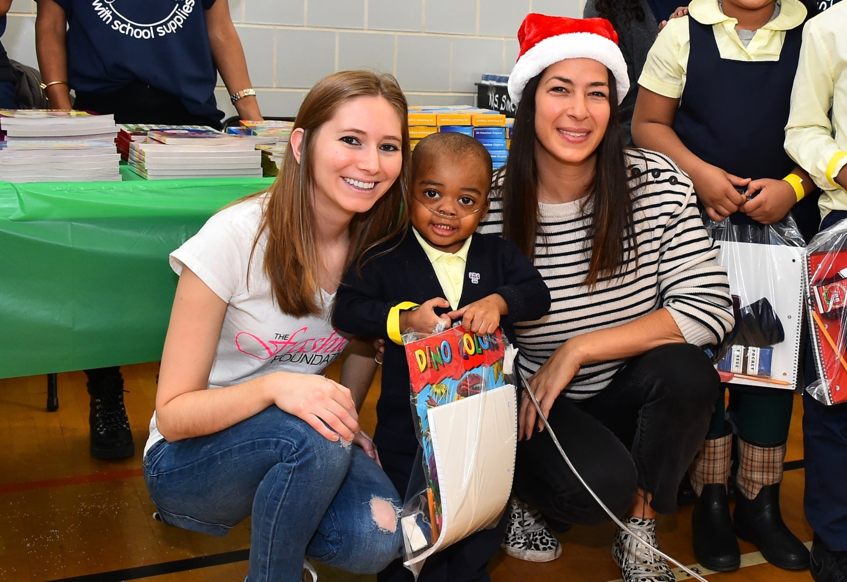 (L to R) The Fashion Foundation founder Amanda Munz, a student  at a Brooklyn elementary school who received donated supplies and designer Rebecca Minkoff on December, 2016. (Courtesy of Amanda Munz)