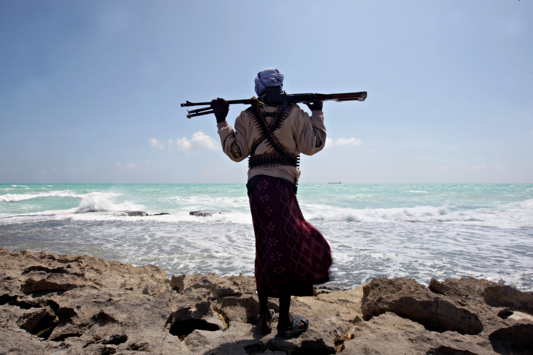 An armed Somali pirate along the coastline while the Greek cargo ship, MV Filitsa, is seen anchored just off the shores of Hobyo town in northeastern Somalia where its being held by pirates on January 7, 2010.  (AFP PHOTO/ MOHAMED DAHIR)