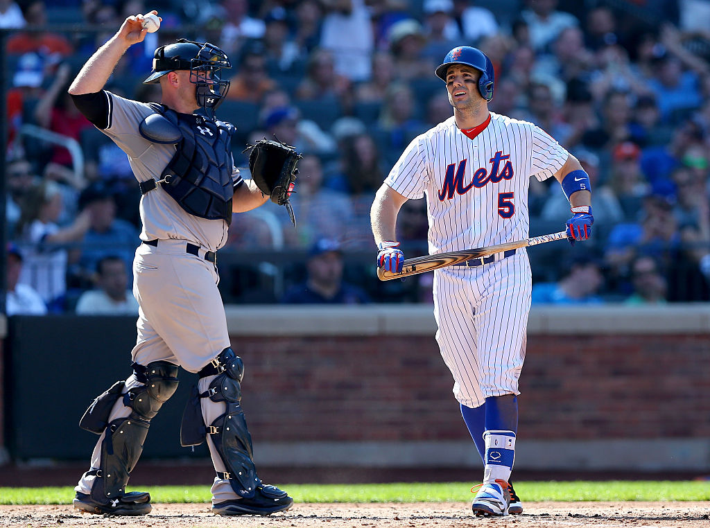 David Wright #5 of the New York Mets walks back to the dugout past Brian McCann #34 of the New York Yankees after Wright struck out with bases loaded in the seventh inning during interleague play on September 19, 2015 at Citi Field in the Flushing neighborhood of the Queens borough of New York City. (Photo by Elsa/Getty Images)