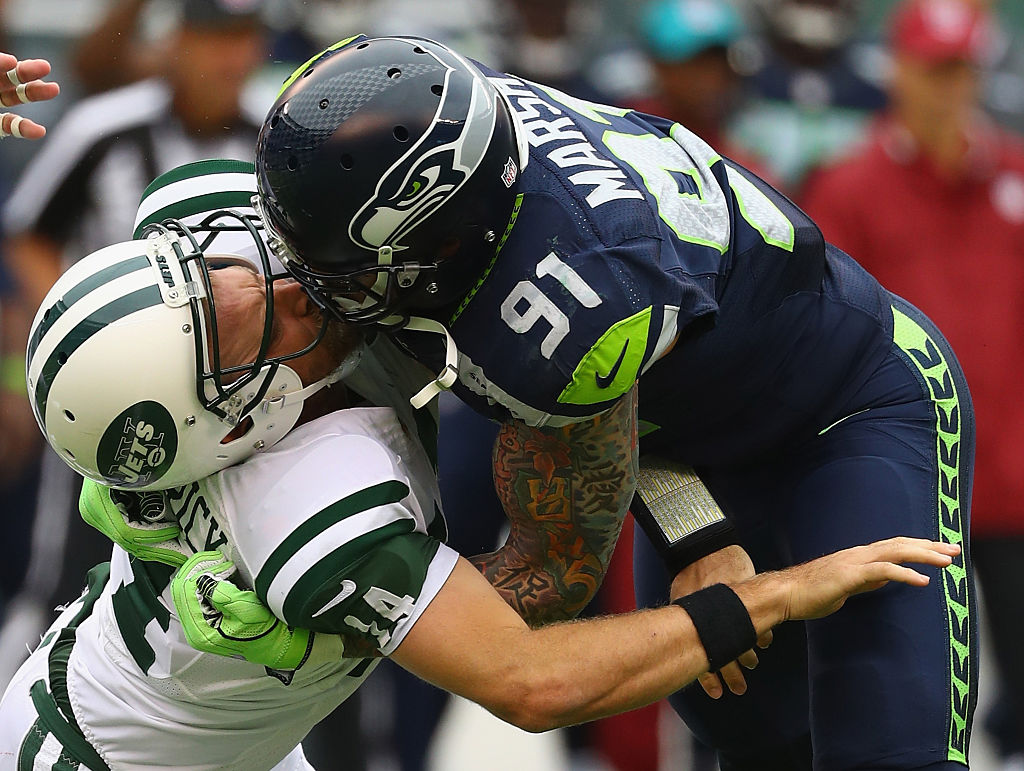 Cassius Marsh #91 of the Seattle Seahawks hits his helmet against quarterback Ryan Fitzpatrick #14 of the New York Jets for a penalty 'Roughing the Passer' in the second quarter at MetLife Stadium on October 2, 2016 in East Rutherford, New Jersey.  (Photo by Al Bello/Getty Images)