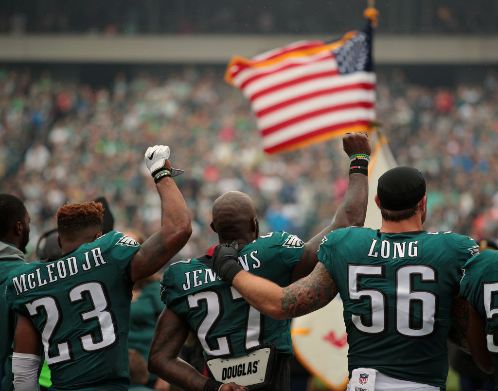 PHILADELPHIA, PA - OCTOBER 08: Rodney McLeod #23, Malcolm Jenkins #27 of the Philadelphia Eagles raise their fists in protest during the playing of the National Anthem as teammate Chris Long #56 shows support before a game against the Arizona Cardinals at Lincoln Financial Field on October 8, 2017 in Philadelphia, Pennsylvania. (Photo by Rich Schultz/Getty Images)