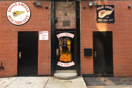 "A sign near the front door of the Hells Angels motorcycle club headquarters in New York reads ""No Parking Except Authorized Hells Angels,"" Friday, Dec. 16, 2016. Earlier in the week an out-of-town man was shot after moving an orange cone meant to save a parking space for club members. The secretive group has frustrated police by refusing to help identify the shooter. (AP Photo/Tom Hays)"