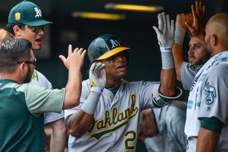 Khris Davis #2 of the Oakland Athletics is congratulated in the dugout after hitting a seventh inning solo homerun against the Colorado Rockies during interleague play at Coors Field on July 29, 2018 in Denver, Colorado.  (Photo by Dustin Bradford/Getty Images)