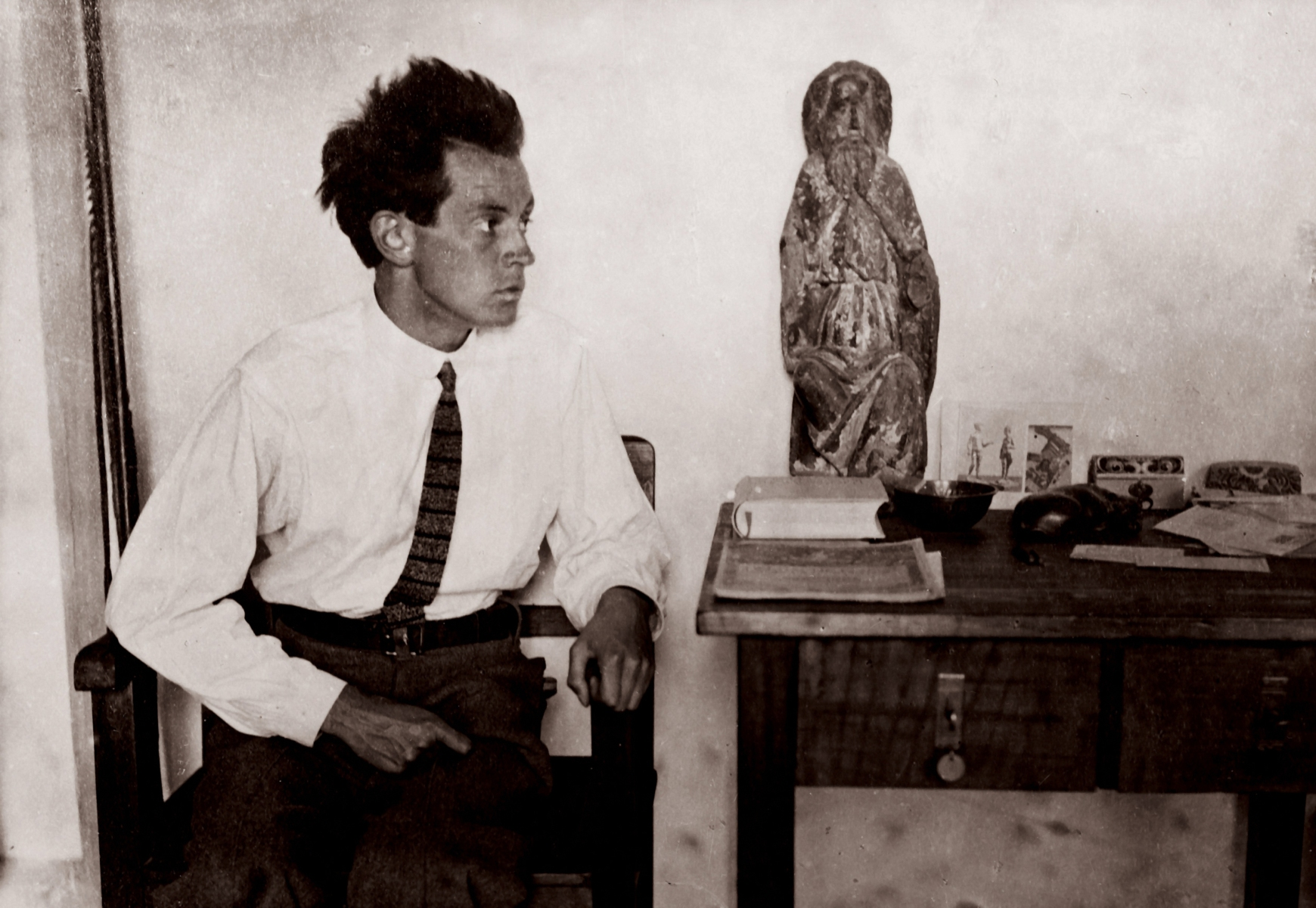 Egon Schiele with a Madonna figure in his studio in Vienna's 13th district. Photography, around 1915.