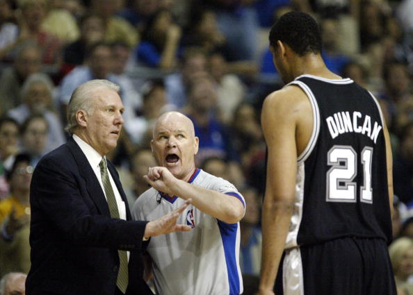 AUBURN HILLS, UNITED STATES:  Tim Duncan (R) of the San Antonio Spurs tries to talk with offical Joe Crawford (C) as head coach Gregg Popovich (L) listens during their game against the Detroit Pistons during the first half of game three of the NBA Finals 14 June, 2005 at The Palace in Auburn Hill, Michigan. (JEFF HAYNES/AFP/Getty Images)