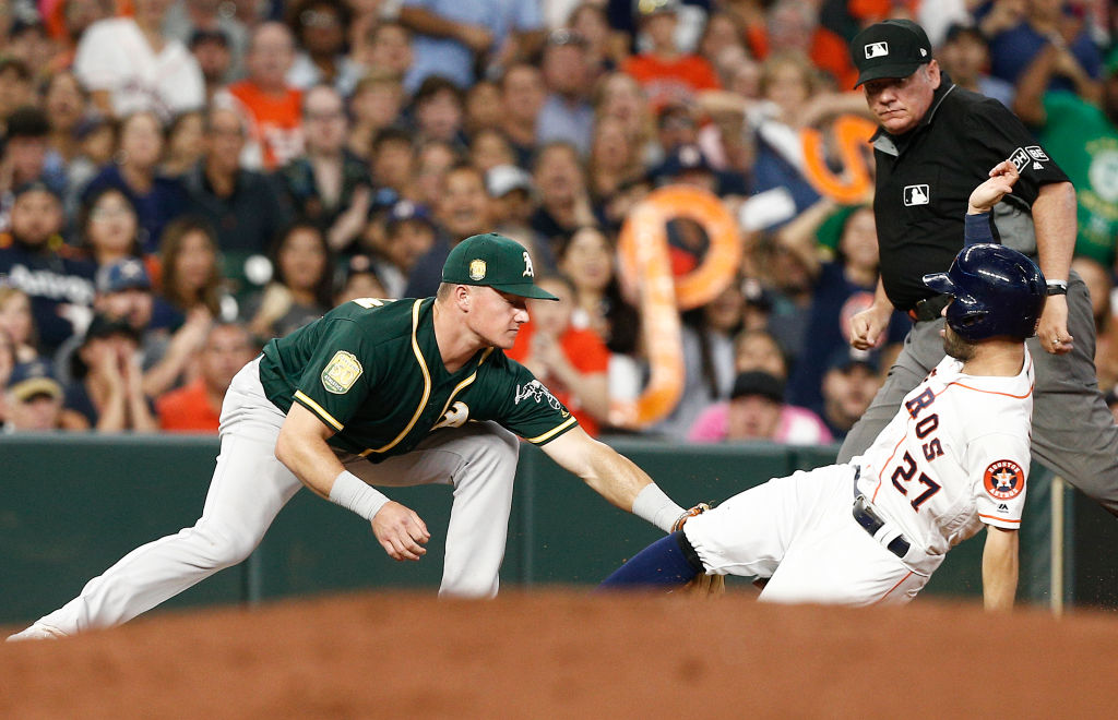 HOUSTON, TX - JULY 09:  Matt Chapman #26 of the Oakland Athletics tags out Jose Altuve #27 of the Houston Astros as he tried to advance on passed ball in the fourth inning at Minute Maid Park on July 9, 2018 in Houston, Texas.  (Photo by Bob Levey/Getty Images)