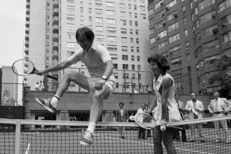 [Original caption] Wimbledon whiz Billie Jean King is glad to lend a hand to a doddering 55-year-old-Bobby Riggs as he hops over net at E. 56th St. court. Bobby and Billie have a date for a $100,000 match one of these days and it's made more interesting in that Billie seems to think Bobby might be some kind of male chauvinist. (Jim Garrett/NY Daily News via Getty Images)
