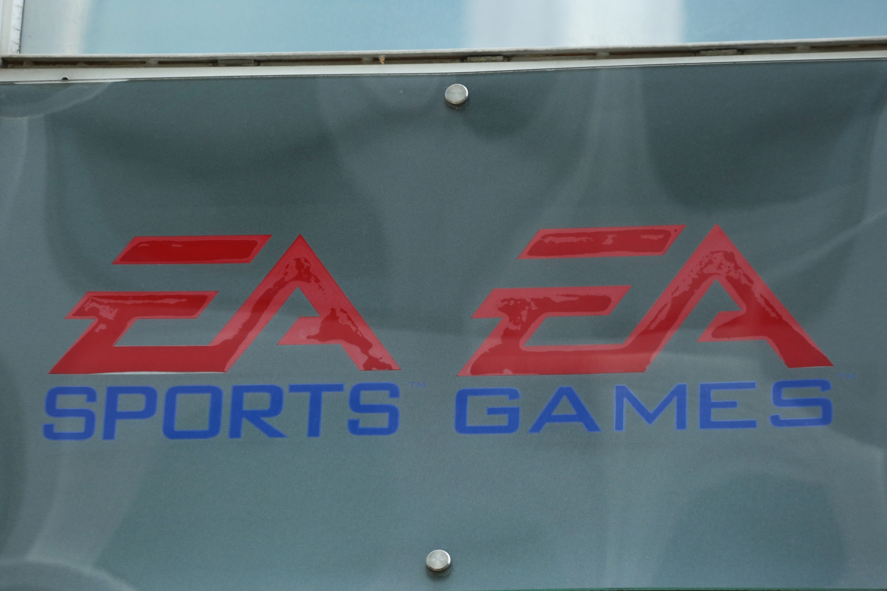 The logo of the American video game company Electronic Arts and its sports game brand EA Sports headquartered in Redwood City, California is seen in the Munich pedestrian zone. EA Sports' Madden game often draws criticism from athletes for its player ratings. (Photo by Alexander Pohl/NurPhoto)