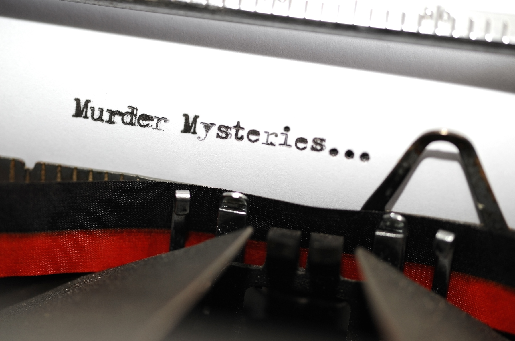 """Book Genre Series:Two words 'Murder Mysteries', intended to be a book genre, picked out on an old and very grungy typewriter. Macro image with differential focus centred on the word 'murder'."""