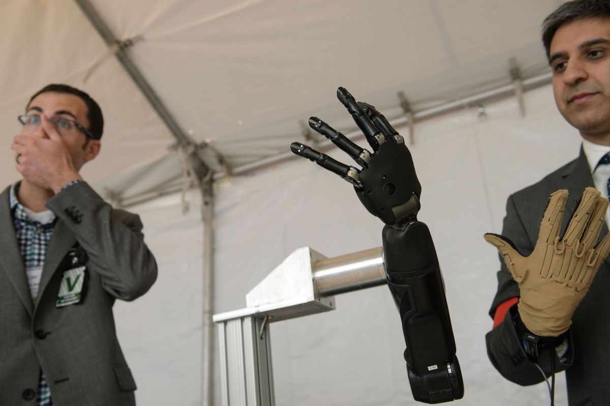 Exhibitors from Johns Hopkins Applied Physics Laboratory  stand with a robotic hand during the Defense Advanced Research Projects Agency (DARPA) Demo Day at The Pentagon on May 11, 2016 in Washington, DC. Darpa's continuing research into neurotechnology is currently prompting ethical questions about its potential military applications. (Photo by BRENDAN SMIALOWSKI/AFP/Getty Images)