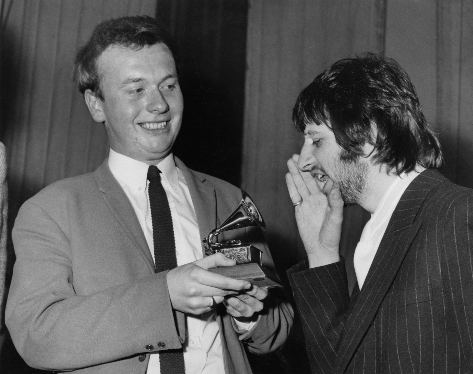Drummer Ringo Starr of English congratulates EMI recording studio audio engineer Geoff Emerick (left) on his Grammy Award at the EMI studios in London, 7th March 1968. Emerick recently passed away at the age of 72. (Photo by Monti Spry/Central Press/Hulton Archive/Getty Images)
